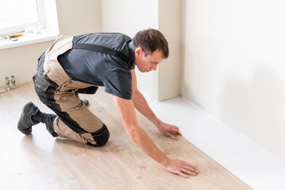 man installing new wooden laminate flooring