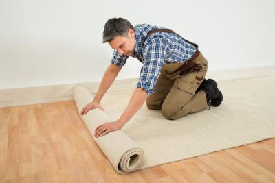 male worker unrolling carpet on floor