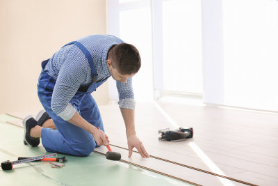 man installing vinyl on floor